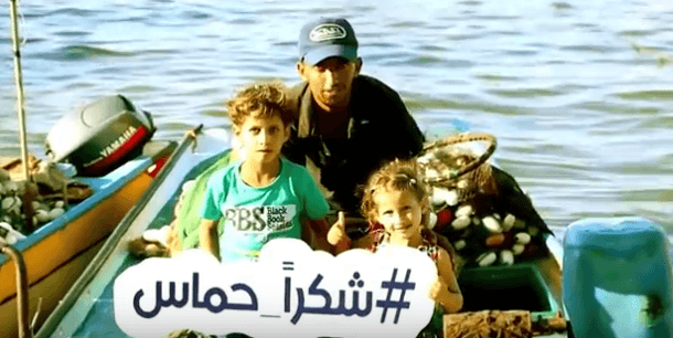 A Gazan family holds a sign reading #Thank You Hamas. (Video Screenshot)