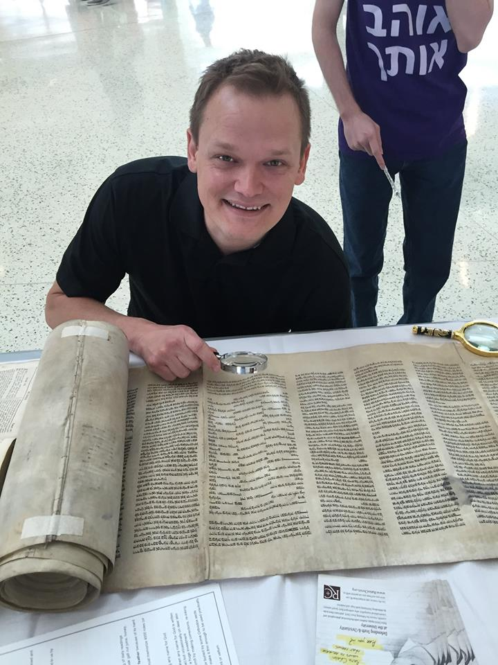 A student examines the Torah scroll (Ratio Christi Facebook Page)