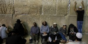 Orthdox Jewish men sit in mourning for the destruction of the Temple on Tisha B'Av at the Wall Western in the Old City of Jerusalem. (Yonatan Sindel/Flash90)