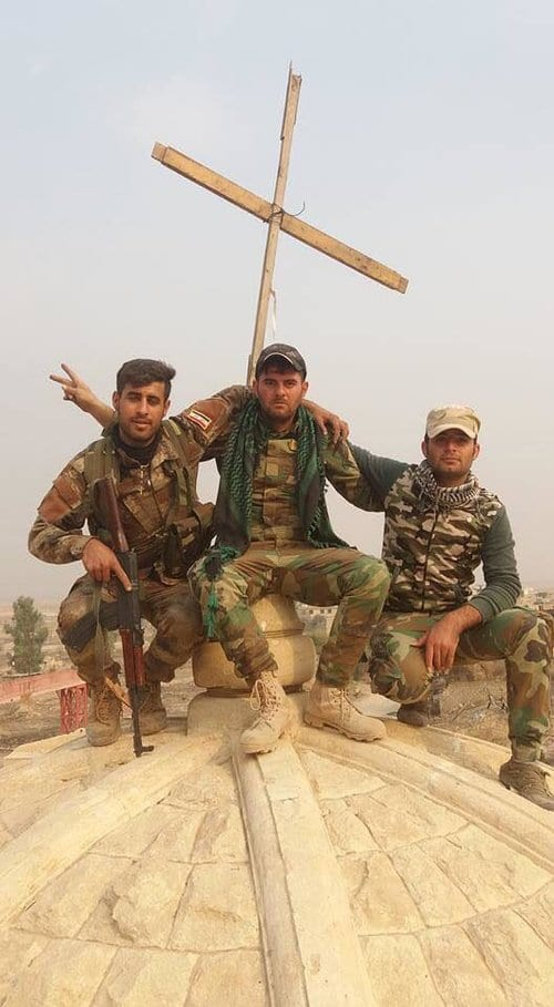 Assyrian Christian pose in front a newly erected cross atop the Mar Shmony church in the liberated town of Bartella, Iraq. (Nineveh Plains Protection Unit)