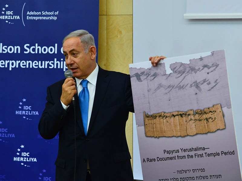 PM Netanyahu holds a close-up view of the papyrus at the dedication of the Adelson School of Entrepreneurship at IDC Herzliya. (GPO/Kobi Gideon)