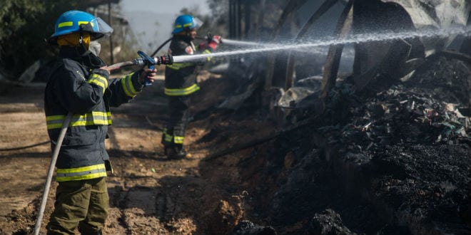 Fire fighters work to extinguish a fire in a factory which was burnt in an overnight fire in Beit Meir, outside of Jerusalem on November 25, 2016. (Hadas Parush/Flash90)