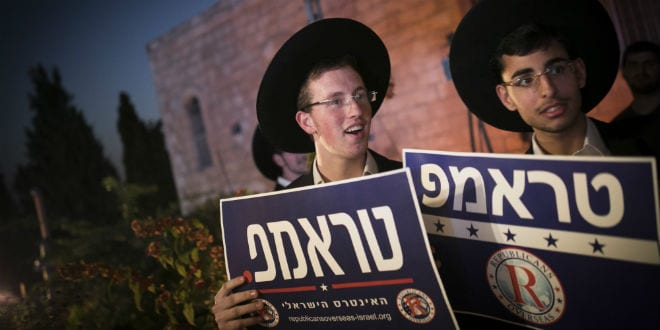 Ultra-Orthodox Jewish men hold placards as they attend an election campaign conference supporting US Republican presidential candidate Dondald Trump, in Jerusalem on October 26, 2016. (Yonatan Sindel/Flash90)