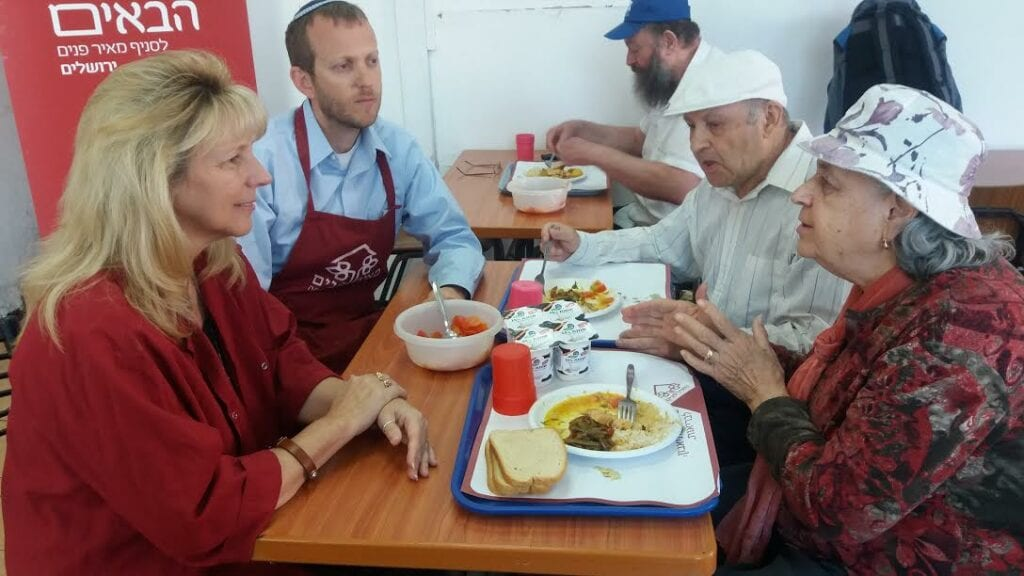 Rabbi Tuly Weisz speaks to Holocaust survivors at a soup kitchen. (Israel365)