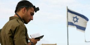 An IDF soldier on the southern military base of Zikim prays with tefillin. (Edi Israel/Flash90)